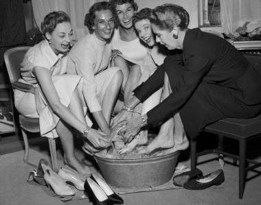 """""""Vi maa slanke os - for Moden siger lange Ben og smalle Hofter""""skriver B.T. efter at have været til modeopvisning hos Illum den 30. august 1955. B.T. var også bag scenen for at hilse på modellerene:""""Undersaatterne køles - Det gælder for Mannequiner som for Balletdanserinder - Man maa være paa Tæerne. I Gaar begyndte de store Opvisninger (læs mere paa Damesiden), og i Tropevarme og paa Stilethæle maatte de arme Mannequiner vise os det sidste nye i Uld og Pelsværk og dog se kølige og ladylike ud. Men Futterne kunne kun bringes tilbage til normal Størrelse mellem Numrene via intimere Omgang med en Balje med store Isblokke. Her har de Mannequinerne Aase Ehlers, Birte Amter, Ruth Gjersøe, Fru Solveig og Fru Yelva omkring Baljen med den liflige Is"""".; Behind the scene at a fashion show. The mannequins Aase Ehlers, Birte Amter, Ruth Gjersøe, Mrs. Solveig and mrs. Yelva cool their feet in a tub with ice cold water between the performances.;"""
